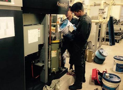 nhân viên kỹ thuật thay dầu máy nén khí